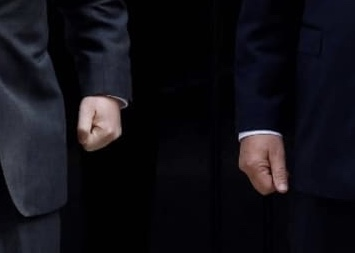 photo of two clenched fists that belong to (male) bureaucrats